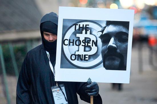 2015年,罗斯·乌布利希在纽约参加庭审时的一位抗议者(举着牌子)。法警局第一次拍卖的加密货币就是缉毒行动从罗斯·乌布利希身上缴获的比特币。Spencer Platt—Getty Images